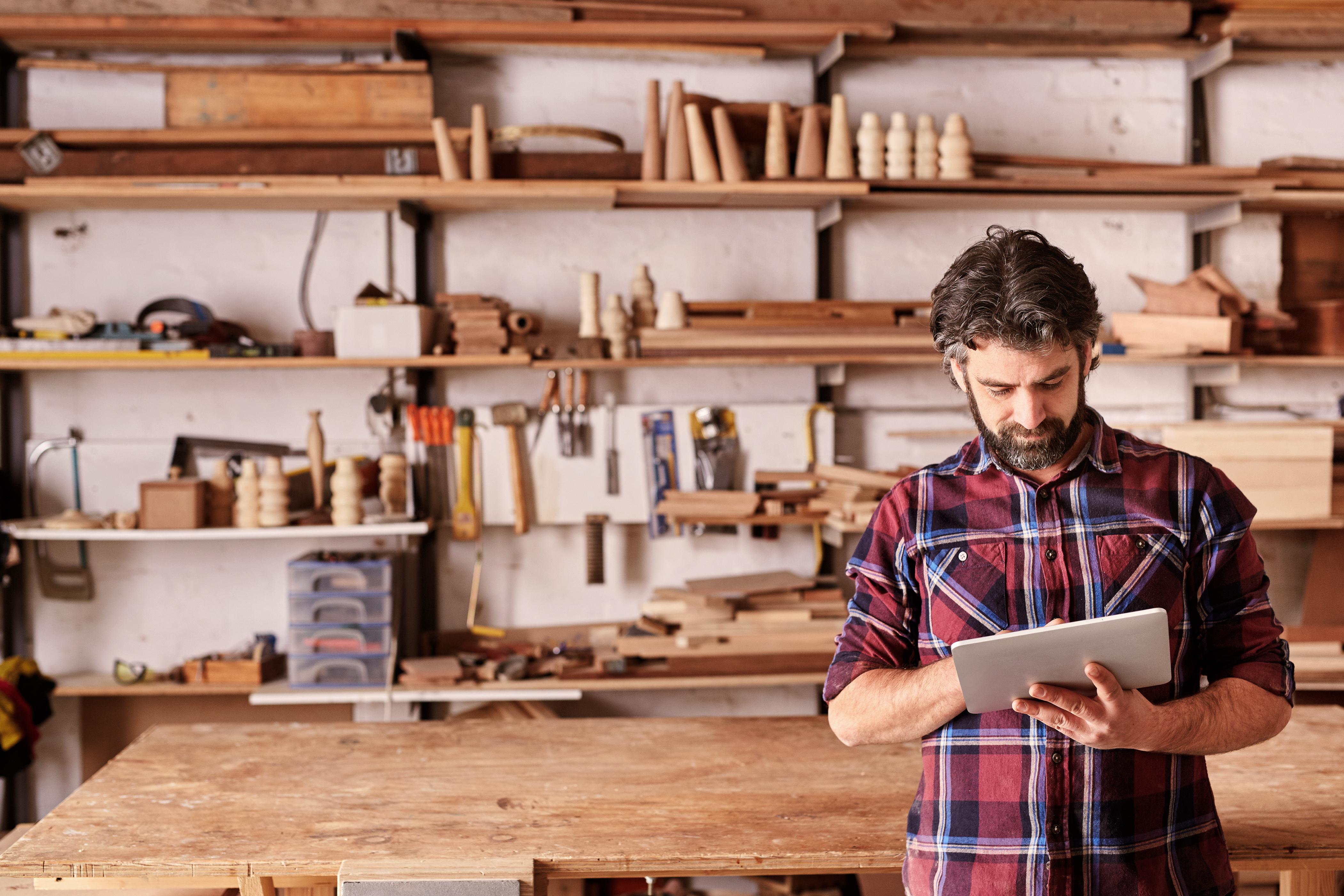 Man in workshop buying woodworking tools online.