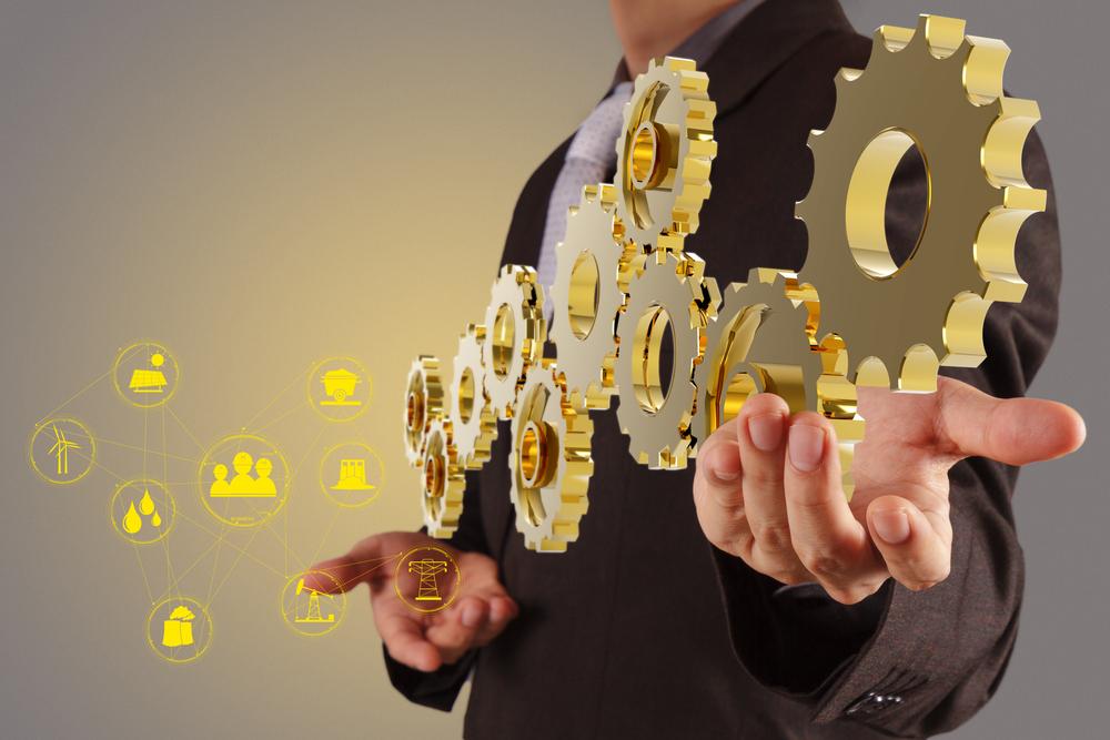 Businessman holds 3D gold components.