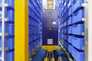 Image of Automated warehouse machine restocking blue shelf cartons.