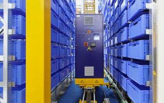 Image of Automated warehouse machine restocking blue shelf cartons.