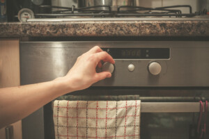 A woman cooking, turning a metal hand knob on an oven.