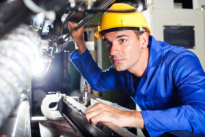 A photo of an industrial worker in a factory looking at industrial components