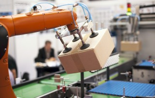 Image of packaging machine with new industrial components lifting a cardboard box.